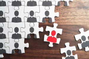 Ein Puzzleteil mit roter Person inmitten von Puzzleteilen mit grauen Personen.